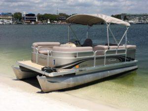 Economical pontoon boat beached on destin harbor